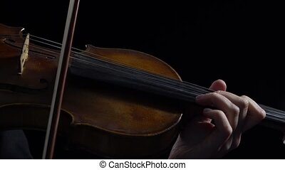 Women play strings of a violin in a dark room. Black background. Close up