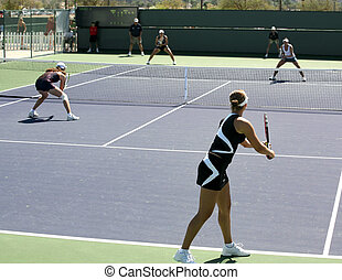 Women playing doubles - Four women playing doubles at the...