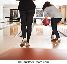 Women Playing in Bowling Alley - Rear view of young women...