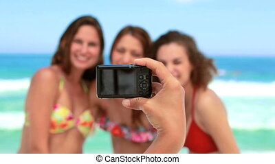 Women posing for a photo on the beach