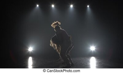 Women practicing capoeira in darkness against spotlight in...