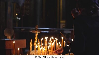 Women prays and burns candles in slow motion in the Church...