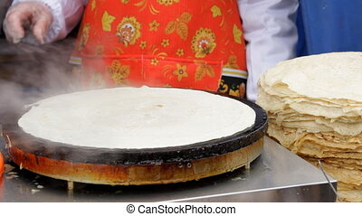 Women prepare pancakes in the street