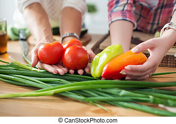 Women preparing dinner in a kitchen holding vegetables hands concept dieting healthy food cooking at home.