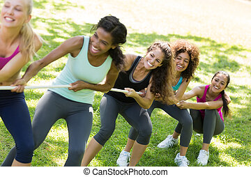 Women pulling a rope in tug of war - Excited women pulling a...