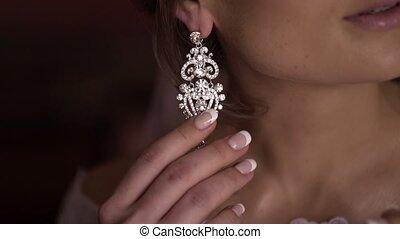 Women puts on earrings closeup
