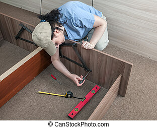 Women putting together self assembly furniture.