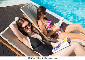 Women reading books on sun loungers by swimming pool - Side...