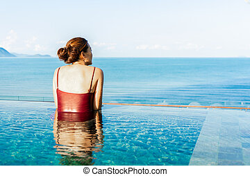 Women relax in swimming pool with mountain view and sunrise