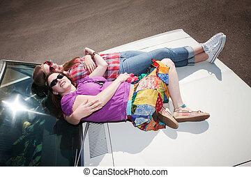 Women resting on a car hood