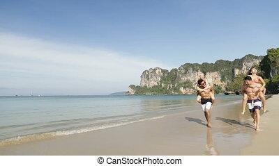 Women Ride Men Running On Beach In Mountains, Two Happy...