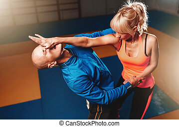 Women self defense technique, workout with personal instructor in gym, martial art