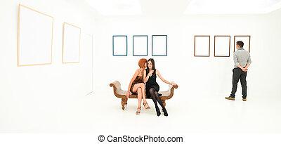 women sharing secrets in an art gallery