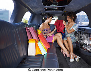 woman in limousine showing new dress to her friend. Horizontal shape, full length, copy space