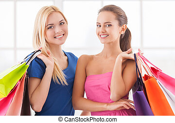 Women shopping. Two beautiful young women in dresses standing close to each other and holding shopping bags