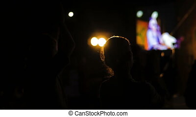 Women silhouette clapping at electronic music concert in...