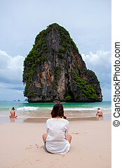 women sit on the beach looking sea and island.