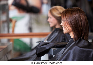 Women sitting in beauty salon.