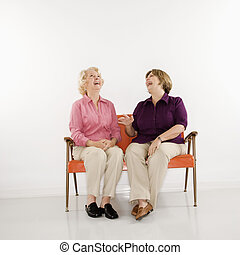 Women sitting laughing.