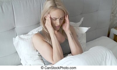 Women sitting on bed holding her head. She has a painful headache