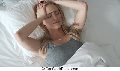 Women sitting on bed holding her head. She has a painful...