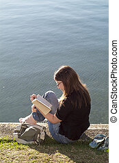 Women sitting on waters edge reading book, Raglan, New Zealand