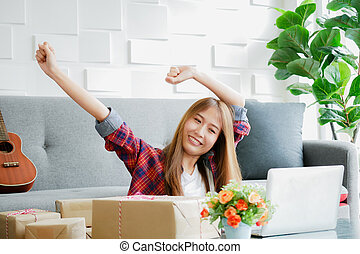 Women smile face with arm raised with the box containing her products to be delivered to customers on desk in the house after video live sells products.
