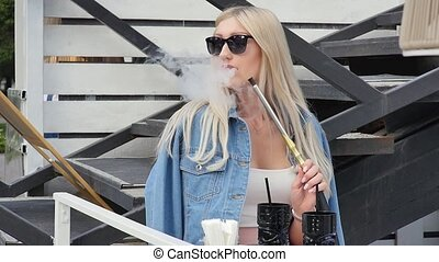 women smoking hookah in open air, woman pull hookah in...