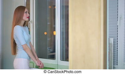 Women standing by the windowsill, looking out of window. night city