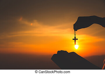 Women standing holding holy  bible and the crucifix for worshipping God at sunset background, Pray to the god, christian silhouette concept.