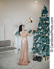 Women standing in a room near a fireplace and Christmas tree