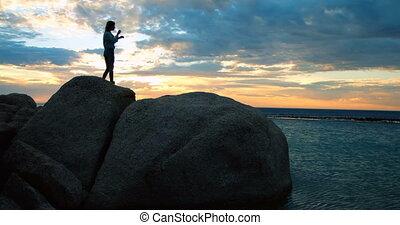 Women standing on rock at beach 4k - Silhouette of women...