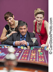 Women standing with man at roulette table