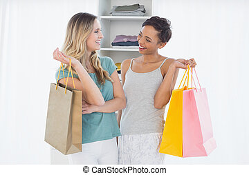 Women standing with shopping bags at home