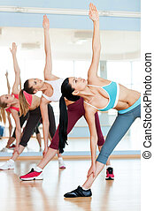 Women stretching. Three beautiful young women in sports clothing stretching while standing in a row