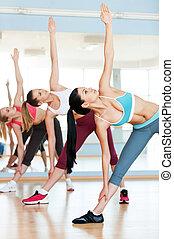 Women stretching. Three beautiful young women in sports ...