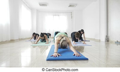 Women students working out their flexibility on a mat during...
