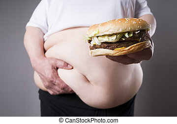 Women suffer from obesity with big hamburger in hand. Junk food concept