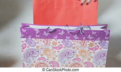 Women taking paper shopping bags of different colors, closeup