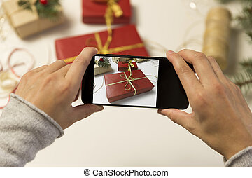 Women taking photo of wrapped gifts for Christmas with smart phone.