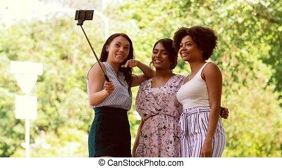 women taking selfie by smartphone in city - friendship,...