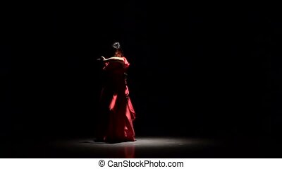 Women the dark room performs elegant movements with her...