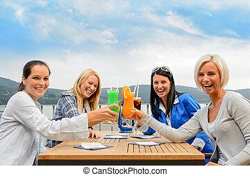 Women toasting cocktails outdoor restaurant terrace - ...