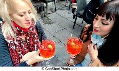 Women with surgical mask, toasting glasses of alcoholic drink cocktail in open pub. Festivity celebration in Coronavirus pandemic with safety social distancing for COVID-19 epidemic. happy hour time.