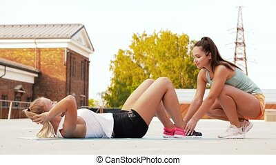 women training and doing sit-ups outdoors - fitness, sport...