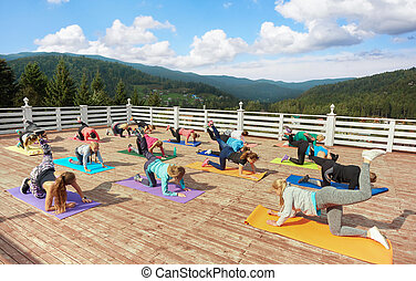 Women training on fitness class, doing exercise on mats.