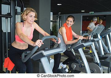 women training on running machine in gym