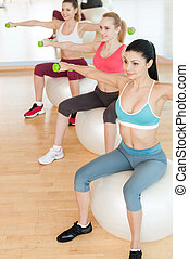 Women training with dumbbells. Top view of three beautiful young women in sports clothing holding dumbbells while sitting on the fitness ball