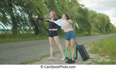 Women travelers hitchhiking with cardboard sign - Cheerful...