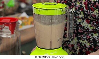 Women turn on blender with milkshake